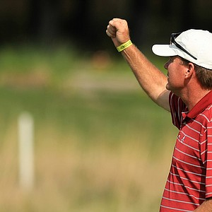 Alabama head coach Jay Seawell, signals back to Cory Whitsett after learning they defeated LSU during Tuesday semifinals of match play of the NCAA Men's Division 1 Championship at Prairie Dunes Country Club in Hutchinson, Kan.