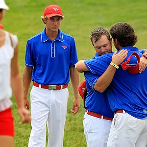 SMU coach Josh Gregory hugs his players after they lost to Alabama during Tuesday quarterfinals of match play of the NCAA Men's Division 1 Championship at Prairie Dunes Country Club in Hutchinson, Kan.