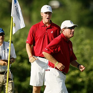 Alabama coach Jay Seawell and Trey Mullinax celebrate winning in the final match play of the NCAA Men's Division 1 Championship between Alabama and Oklahoma State at Prairie Dunes Country Club in Hutchinson, Kan.