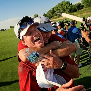 Alabama head coach Jay Seawell gets a hug and a water shower from Tom Lovelady after the Crimson Tide defeated Oklahoma State in the final match at the NCAA Championship at Prairie Dunes Country Club in Hutchinson, Kan.