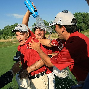 Alabama assistant coach Mike McGraw is doused with water during a TV interview after Alabama defeated Oklahoma State in the NCAA Men's Division 1 Championship between Alabama and Oklahoma State at Prairie Dunes Country Club in Hutchinson, Kan. McGraw used to be Oklahoma State head coach.