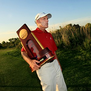 Alabama assistant coach Mike McGraw carries the NCAA trophy after picture sessions with the media at Prairie Dunes Country Club in Hutchinson, Kan.