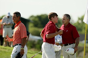 Former Oklahoma State coach, Mike McGraw, right, now assistant with Alabama, congratulates his player, Robby Shelton, during Wednesday final match play of the NCAA Men's Division 1 Championship between Alabama and Oklahoma State at Prairie Dunes Country Club in Hutchinson, Kan. At left is current Oklahoma State head coach, Alan Bratton.(