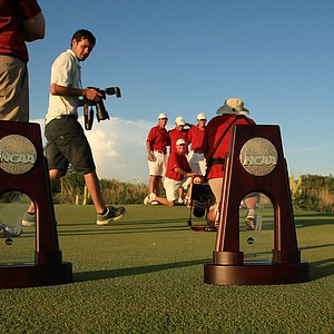 Alabama poses for pictures (background) after winning the NCAA Men's Division 1 Championship against Oklahoma State at Prairie Dunes Country Club in Hutchinson, Kan.