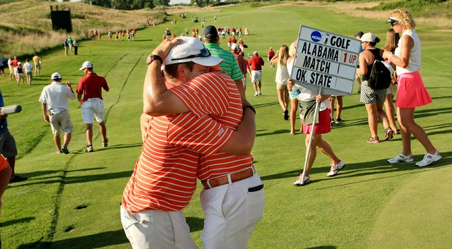 Oklahoma State assistant coach Brian Guetz tries to console Ian Davis after he lost his match to Alabama's Trey Mullinax during the NCAA Men's Division 1 Championship at Prairie Dunes Country Club.
