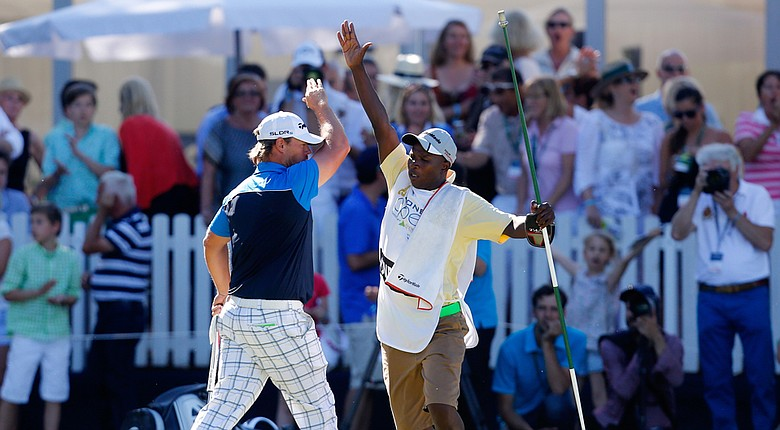 Mikael Lundberg of Sweden celebrates with his caddie after holing a birdie putt in a playoff to win the Lyoness Open.