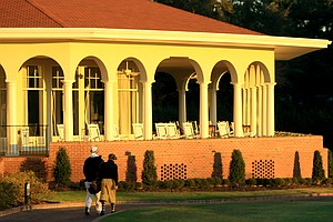 Player and caddie walk to the first hole at Pinehurst No. 2.