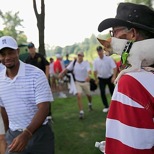 Tiger Woods walks past a fan who brought a dog to the pro-am round at the PGA Tour's 2014 Quicken Loans National.