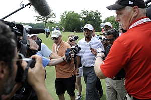 Tiger Woods copes with media during the pro-am round at the PGA Tour's 2014 Quicken Loans National.
