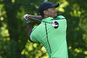 Tiger Woods watches his tee shot on the 14th hole during a first round of the Quicken Loans National.