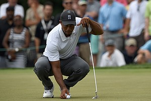 Tiger Woods studies his putt on the first hole on the first hole during the second round of the Quicken Loans National at Congressional.
