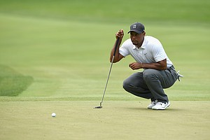 Tiger Woods studies his putt on the third hole during the second round of the Quicken Loans National at Congressional.