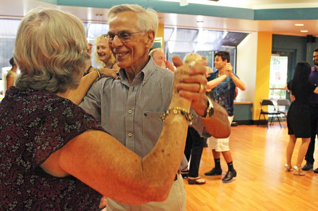 Caregivers and volunteers twirl their partners through choreographed routines.