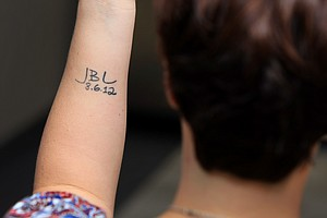 Briony Lyle, Jarrod's wife, shows her tattoo that indicates Jarrod's new birthday, the date of his second bone marrow transplant, June 8, 2012.