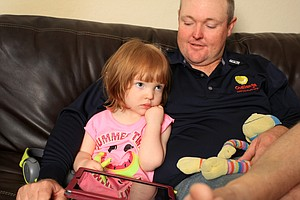 Lusi Joy Lyle, 2, has a little morning time with daddy, Jarrod Lyle and the iPad at their home in Orlando.