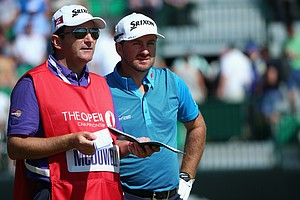 Graeme McDowell chats with his caddie Ken Comboy on the fourth hole during the first round of the Open Championship at Royal Liverpool.