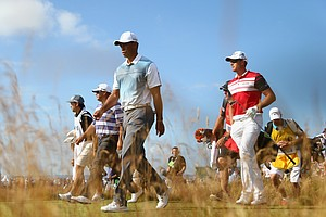 Tiger Woods walks off the second tee with Henrik Stenson during the first round of the Open Championship.