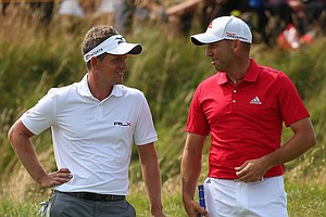 Sergio Garcia chats with Luke Donald of England (L) during the second round of the 2014 British Open.