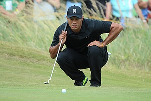 Tiger Woods lines up a putt on the first green during the second round of the 2014 British Open at Hoylake.