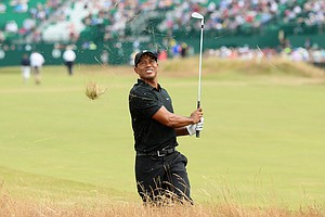 Tiger Woods plays a shot from the rough on the first hole during the second round of the 2014 British Open.