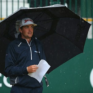 Keegan Bradley shelters under an umbrella as rain falls during the third round of the British Open.