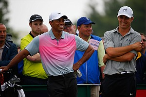 Tiger Woods shares a joke with Jordan Spieth (R) during the third round of the 2014 British Open at Hoylake.