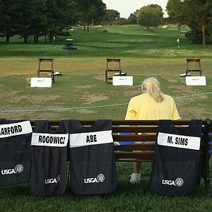 Caddie bibs for the playoff sit on the bench at the range during the 2014 U. S. Women's Amateur at Nassau Country Club.