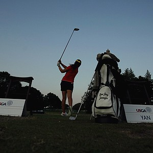 Jing Yan practices as the sun sets behind her at the 2014 U. S. Women's Amateur at Nassau Country Club.
