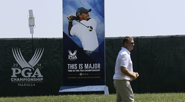 A man walks past a photo of golfer Tiger Woods at the PGA Championship at Valhalla Golf Club. Woods has yet to register for the event, but has until 8:35 a.m. EDT on Thursday morning to do so.