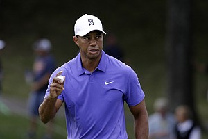 Tiger Woods waves after making a putt on the 12th hole during the first round of the 2014 PGA Championship.
