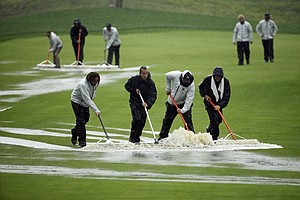 Members of the grounds crew push water off the fairway during the second round of the 2014 PGA Championship.