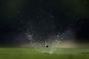 Ryan Palmer's golf tee flies through the rain soaked grass on the 12th hole during the second round of the PGA Championship.