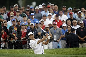 Tiger Woods hits out of the bunker on the first hole during the second round of the 2014 PGA Championship.