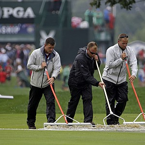 Course workers push rain water off the first hole during a weather delay in final round of the PGA Championship.