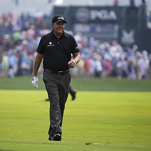 Phil Mickelson smiles as he walks down the fairway on the first hole during the final round of the PGA Championship.