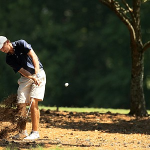 Sam Burns hits a shot from the trees at the second hole while in extra holes during the round of 32 at the 2014 U.S. Amateur at the Atlanta Athletic Club.