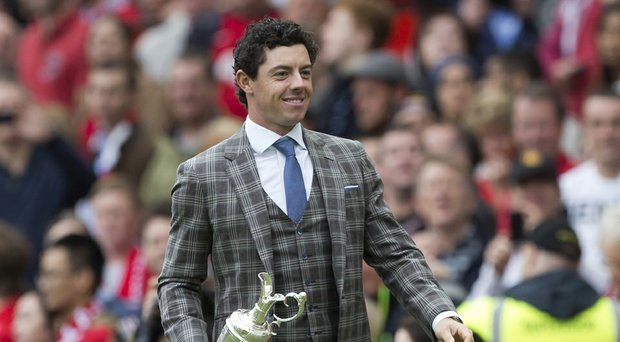 Rory McIlroy showed off the Claret Jug while being honored during halftime of Manchester United's English Premier League opener at Old Trafford.