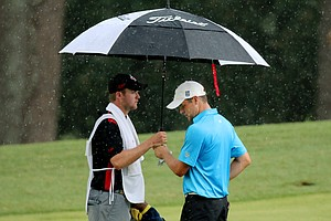 Corey Conners and his caddie Taylor Pendrith as the rain started to come down during the finals at the 2014 U.S. Amateur at the Atlanta Athletic Club.