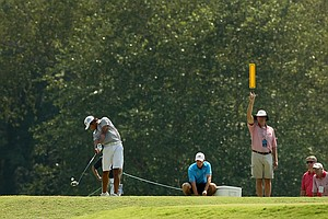 Gunn Yang hits his tee shot at No. 14 as Corey Conners watches, middle, during the finals at the 2014 U.S. Amateur at the Atlanta Athletic Club.
