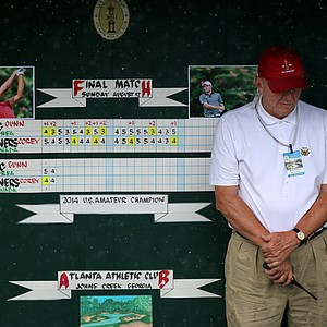 USGA staff member, Mark Passey, takes cover from the rain during the finals at the 2014 U.S. Amateur at the Atlanta Athletic Club.