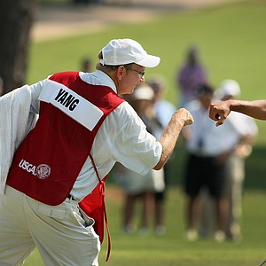 Gunn Yang's caddie, Richard Grice, leans in for a fist bump during the finals at the 2014 U.S. Amateur at the Atlanta Athletic Club.