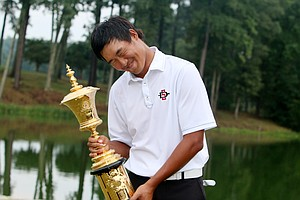 Gunn Yang with the Havemeyer Trophy starts laughing as photographers ask him to kiss the trophy at finals at the 2014 U.S. Amateur at the Atlanta Athletic Club.