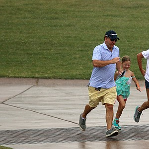 Spectators run back toward the clubhouse pouring rain during the finals at the 2014 U.S. Amateur at the Atlanta Athletic Club.