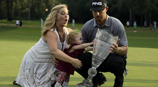 Zoe Mahan, center, pushes the trophy as her mother Kandi Mahan, left, grabs her while they pose with Hunter Mahan, winner of The Barclays.