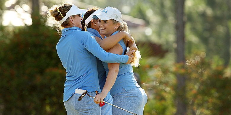 UCLA's Bronte Law being hugged by coaches and teammates.