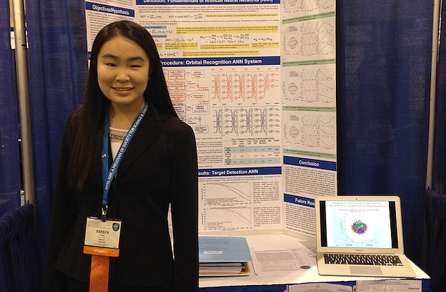 Amber Yang stands in front of her science project which uses computer modeling and data to help satellites avoid space debris. The project was chosen for the Regeneron Science Talent Search.